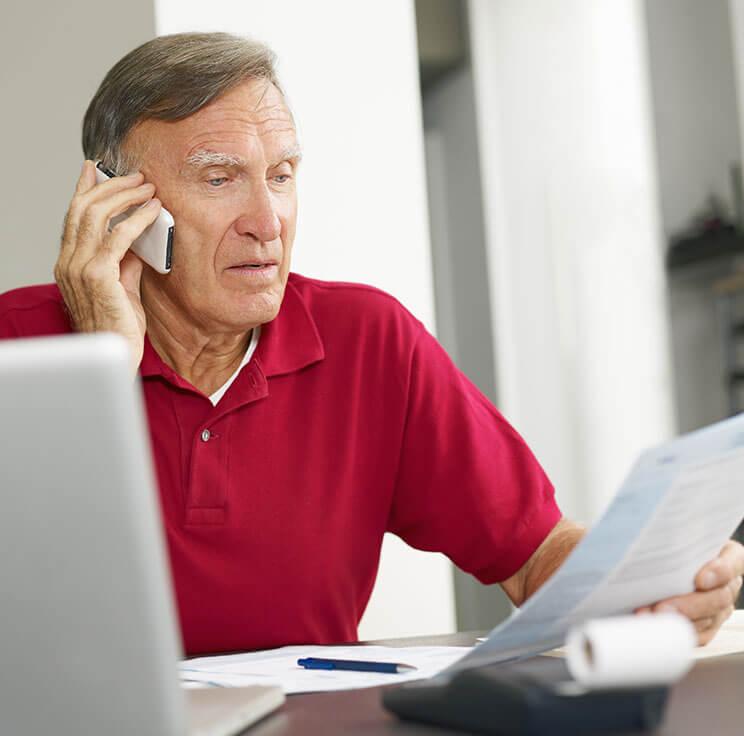 Mies puhuu tietokoneen ääressä puhelimeen ja katsoo kädessään olevaa asiakirjaa.