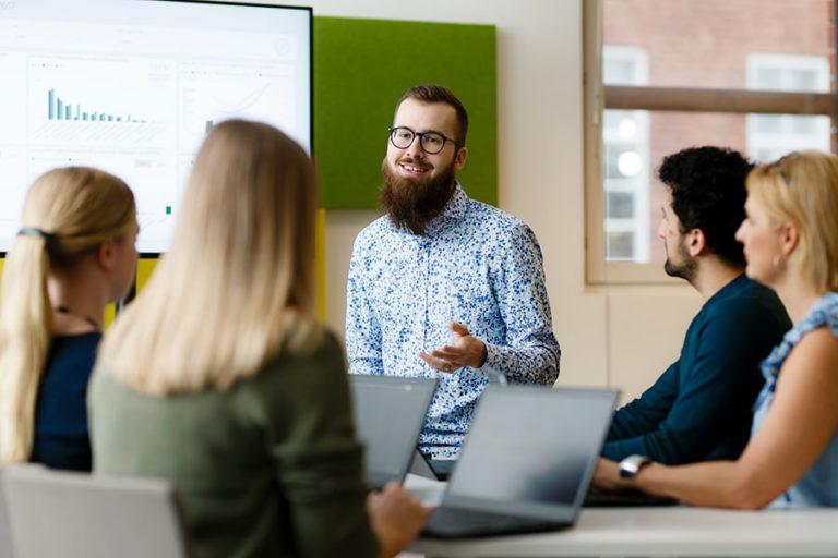 Nuori mies esittelee tilastoja pöydän ääressä istuville kollegoilleen.