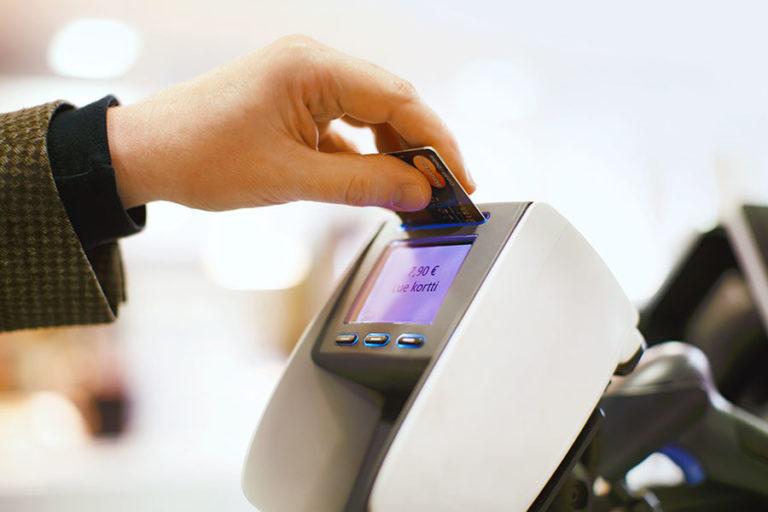 Mies maksaa ostoksia pankkikortilla maksupäätteellä.