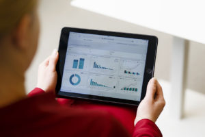 A person holds an iPad that shows statistics.