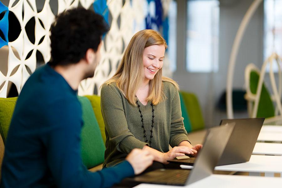 Mies ja nainen työskentelvät kannettavien tietokoneiden ääressä.
