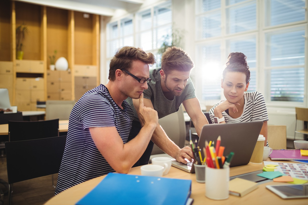 Kolme ihmistä tietokoneen ympärillä tekemässä työtä yhdessä